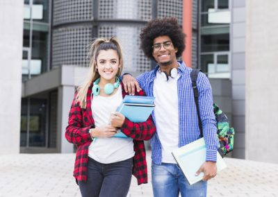 dois-feliz-jovem-estudantes-olhar-camera-ficar-frente-universidade-predios_23-2148093409